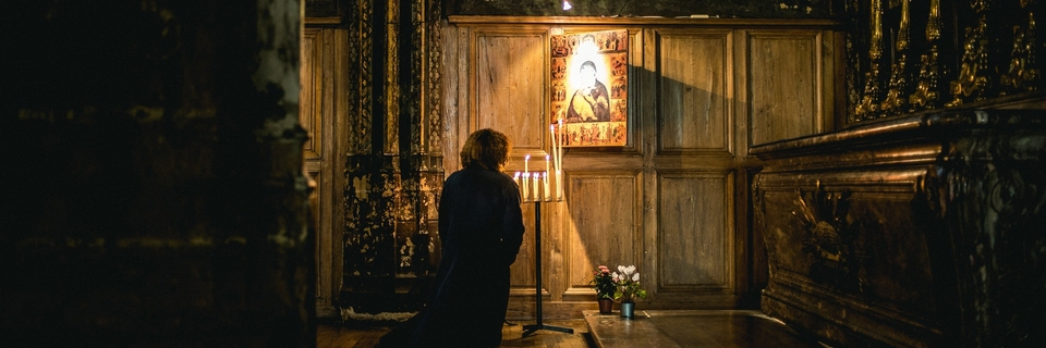 Person praying in a candlelit chapel