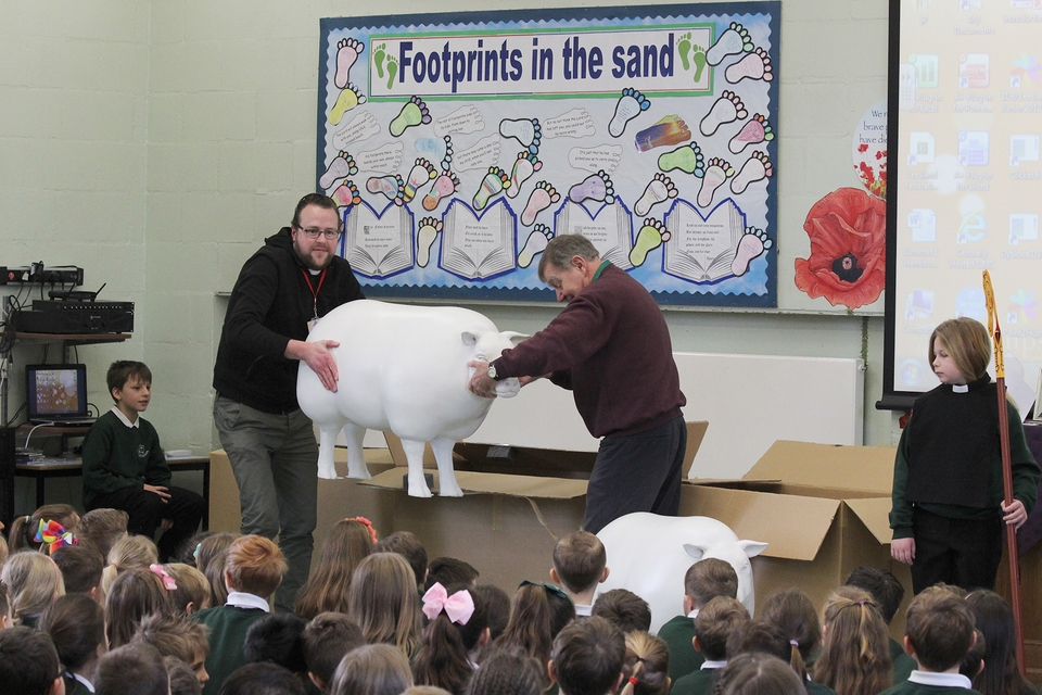 The sheep are unveiled by pioneer minister the Rev Tim Watson and chair of governors Peter Metcalf during the assembly