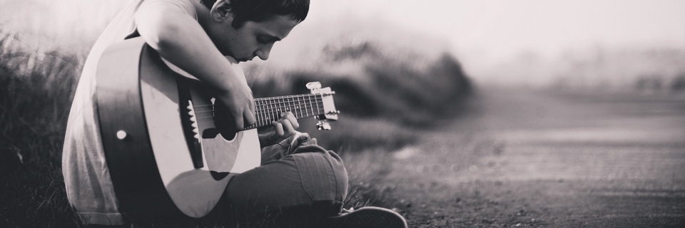 Young person playing an acoustic guitar